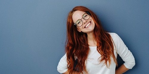 A young female with red hair and glasses tilting her head to the side and smiling