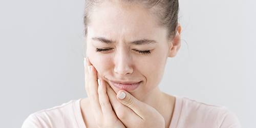 Woman in pink shirt with dental pain
