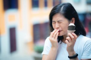 Woman with sensitive teeth covers mouth after eating ice cream