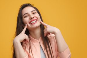 Woman pointing to her smile after teeth whitening treatment.