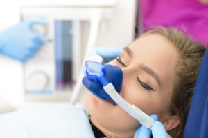 Relaxed woman inhaling nitrous oxide at dentist office
