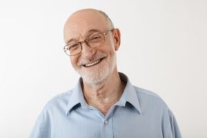Older man with glasses smiling with full set of teeth